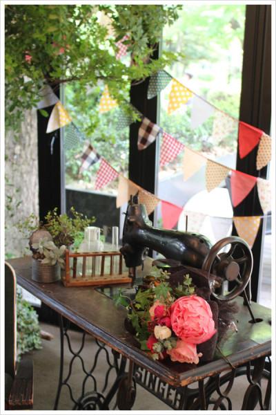 アンティークのミシンには芍薬やオールドローズなどの花束と、ブリキ缶に入れた多肉植物などをディスプレイ。