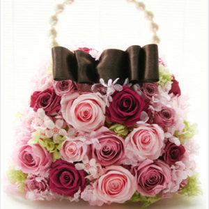 披露宴や二次会でも持ちやすいピンクのバラのバッグブーケ。大きなリボンとパールの持ち手がポイント。