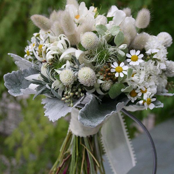 マトリカリア、フランネルフラワーを使った野の花風クラッチブーケ。素朴でナチュラルな雰囲気に。