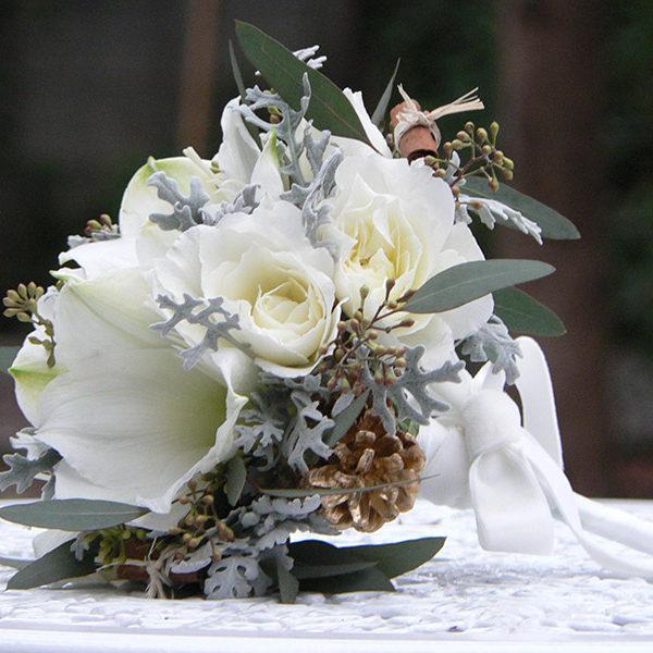 白いアマリリスとバラのブーケ。松かさやシルバーリーフでクリスマスや冬の雰囲気をプラス。