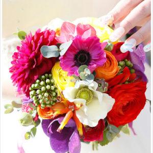 赤いラナンキュラスをはじめ、アネモネやダリアなど様々な色のお花をミックスしたカラフルで個性的なクラッチブーケ。[ レストラン ラファエル様 ]