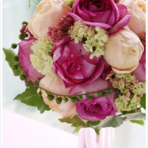 イヴ・ピアッチェとアプリコットカラーのバラのブーケ。粒々の実とグリーンがアクセント。