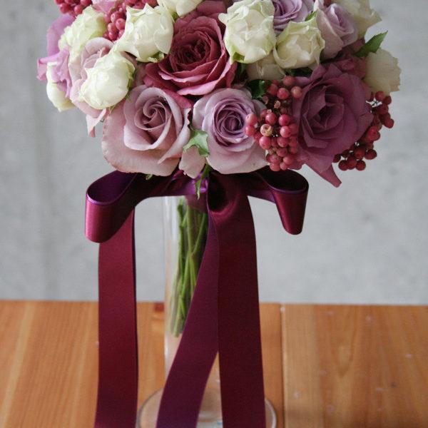 数種類のバラを使い、パープルのグラデーションになるように仕上げたラウンドブーケ。長いリボンがポイント。[ 明治記念館様 ]