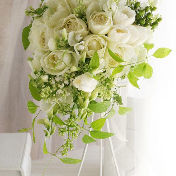 白バラにライラックやスイートピー、ライムグリーンの葉を合わせた、軽やかなセミキャスケードブーケ。