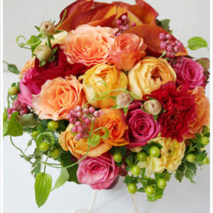 赤、オレンジ、黄色など様々な花を束ねたブーケ。オレンジ色のカラーが個性的な印象。[ レストランFEU様 ]