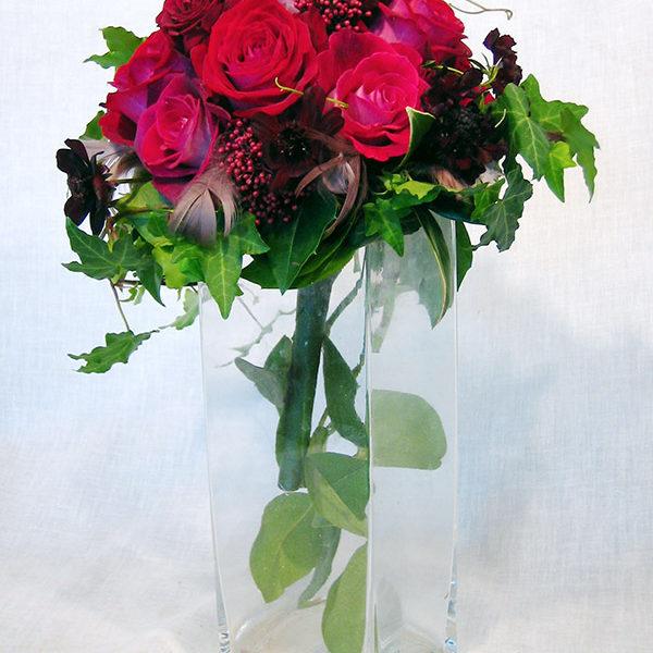 赤いバラにチョコレートコスモスを加えたシックで大人っぽいブーケ。アクセントに羽を散らしてバレンタインらしいロマンチックな雰囲気に。
