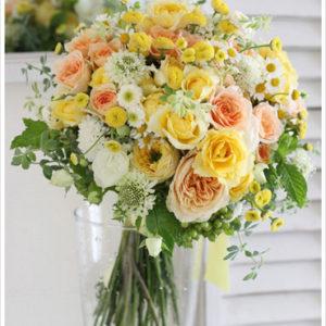 イエローやオレンジ、ホワイトのお花を使い、野の花を束ねたようなナチュラルなクラッチブーケ。