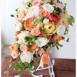 アプリコット色や淡いシャーベットオレンジのバラやラナンキュラスに実ものやグリーンをたっぷり合わせた優しいキャスケードブーケ [ 東京ディズニーシー・ホテルミラコスタ ]
