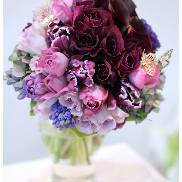 ワイン色のバラやカラーに青紫、赤紫等様々なパープルを重ねたブーケ。ゴールドの蝶を加えてロマンチックな雰囲気に。
