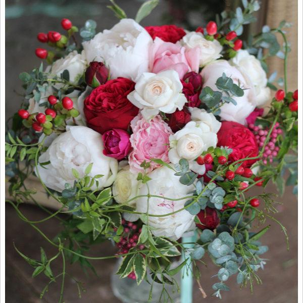 白いシャクヤクと赤いバラを使った大きめのクラッチブーケ。 赤い実やグリーンをざっくりと無造作に束ねて外国風のブーケに。