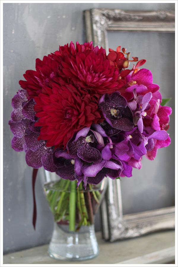 赤いダリアと紫、ワイン、ピンク系の蘭を使った大人っぽいクラッチブーケ。 花材を種類ごとにまとめて入れるグルーピングの手法でモダンでスタイリッシュに。