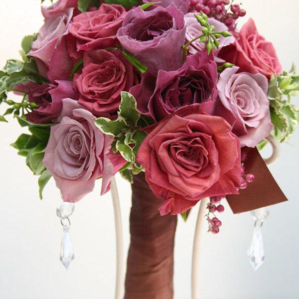 パープルとブラウンのバラのクラッチブーケ。持ち手をブラウンのリボンで巻いてよりシックな雰囲気に。[ 白金 アートグレイスクラブ様 ]