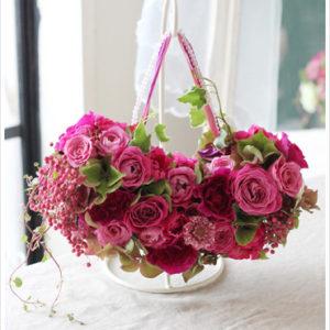 濃いピンクのバラ等を使ったバッグブーケ。垂らした実やビーズの持ち手がアクセント。