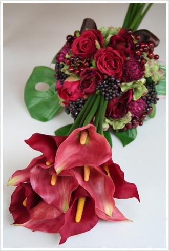 赤いカラーのブーケの手元にバラやベリーを丸くアレンジした変型アームブーケ(アートフラワー)