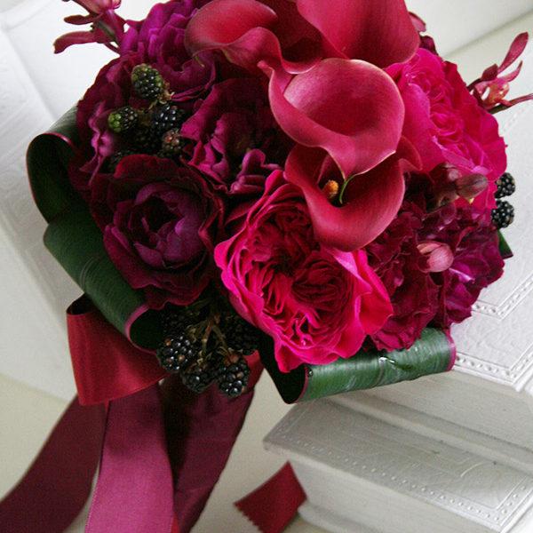 シックなワイン色のカラーにベルベッドのようなこっくりした赤いバラや蘭を合わせたクラッチブーケ。[ ツキ シュール・ラ・メール 様 ]